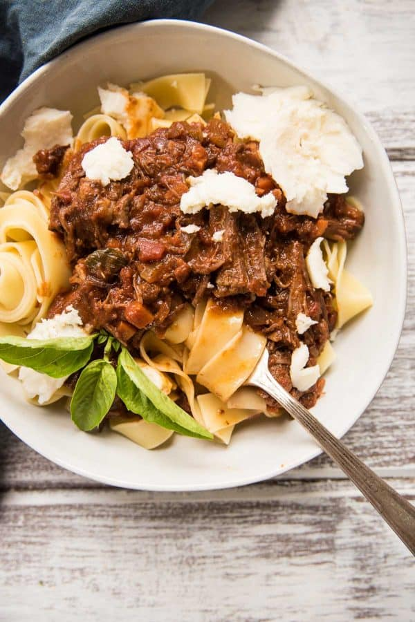 overhead shot of short rib bolognese over pappardelle pasta