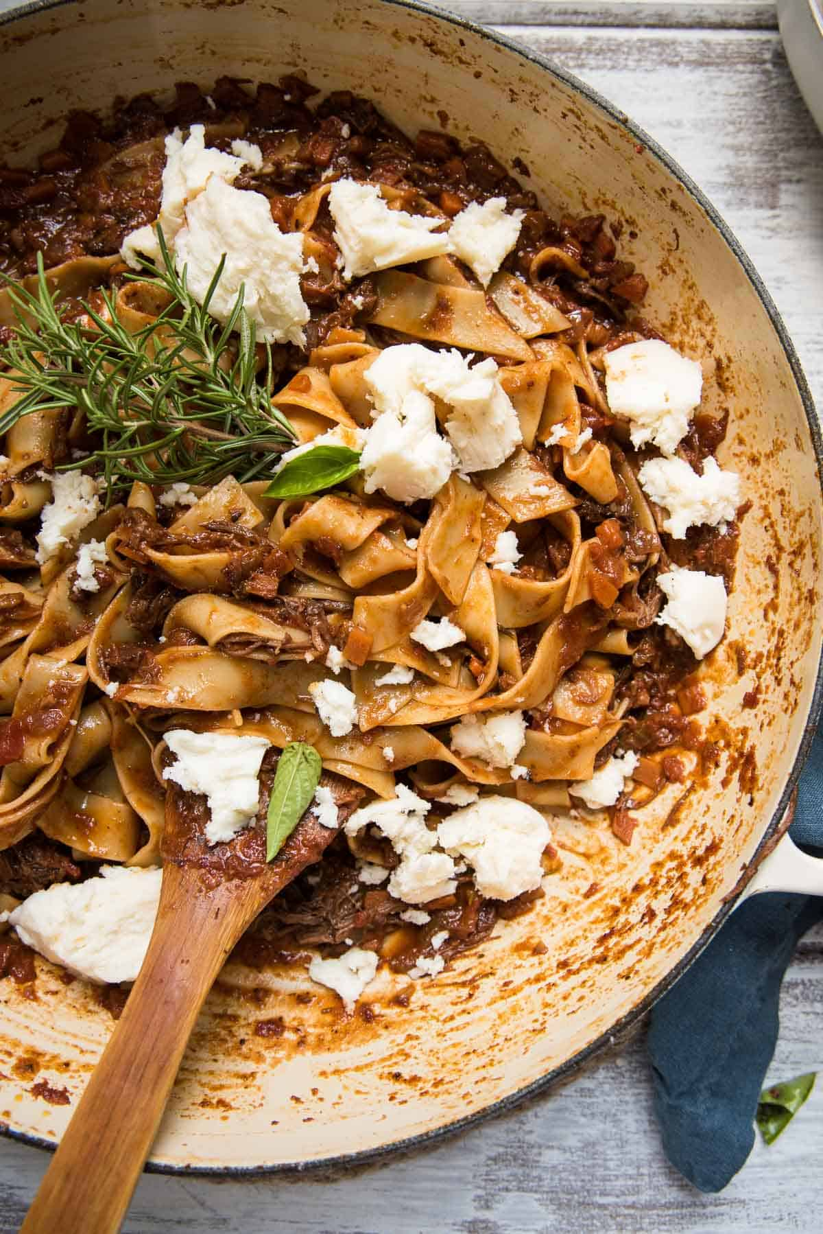 overhead of a pan full of short rib bolognese with pappardelle pasta