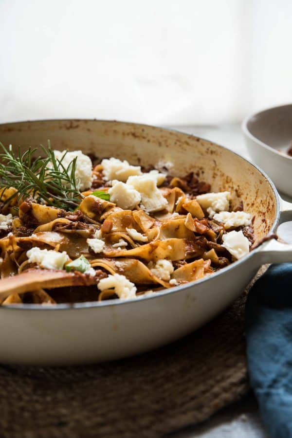 side angle of pappardelle pasta with short rib bolognese in a cast iron braiser