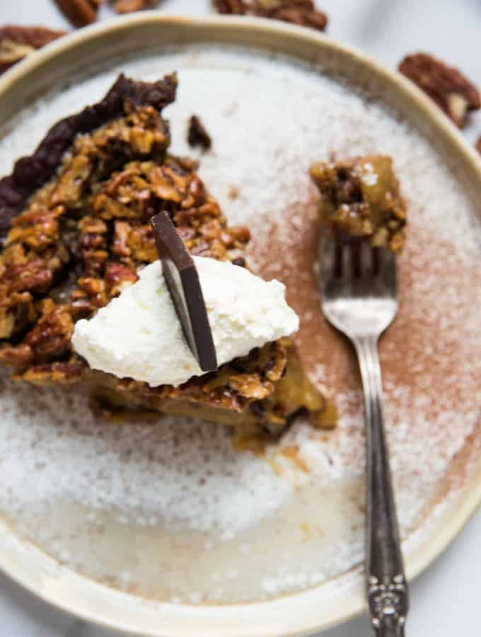 pie topped with whipped cream, chocolate and a forkful of bourbon pecan pie
