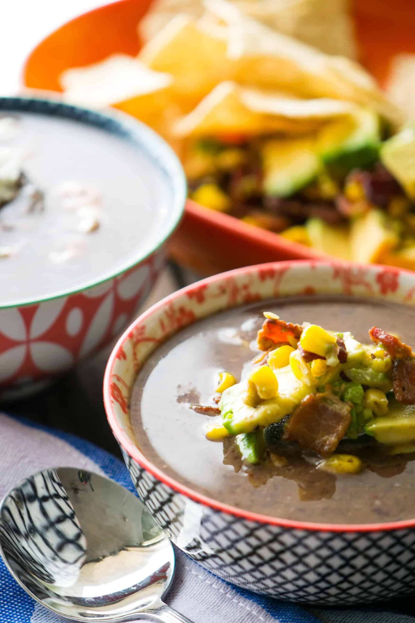 bowls of black bean soup with bacon corn salsa