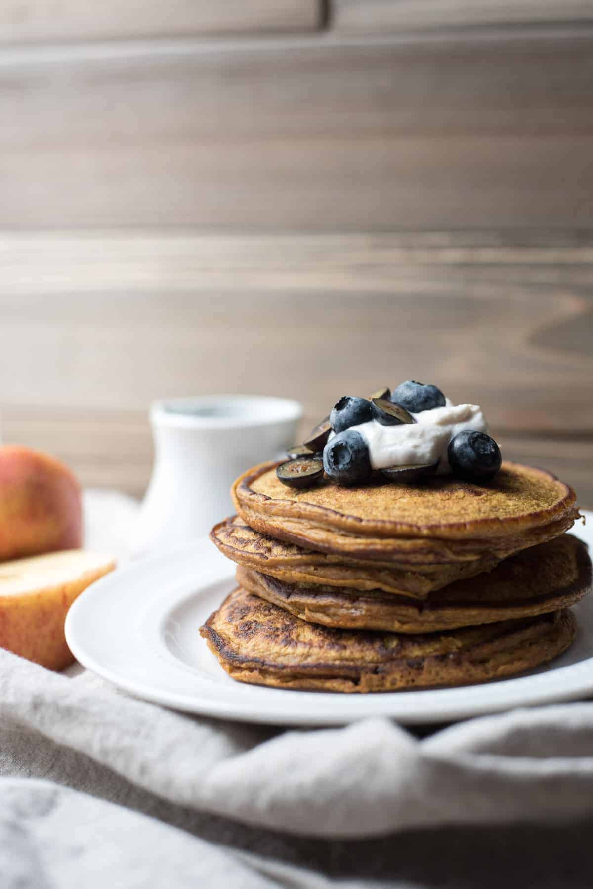 stack of pumpkin spice blender pancakes topped with yogurt and blueberries