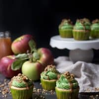 assortment of cupcakes with green apple frosting and black background