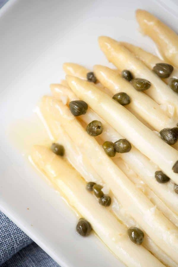 close up of piccata sauce over white asparagus