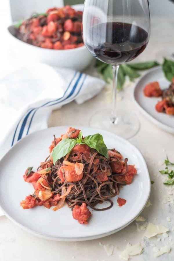 black bean spaghetting with chunky tomato sauce on a plate