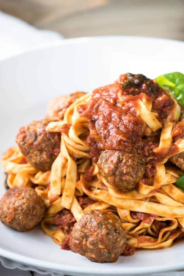 meatballs on top of fresh linguine with extra sauce