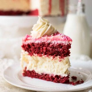 Creamy New York style cheesecake between layers of red velvet cake.