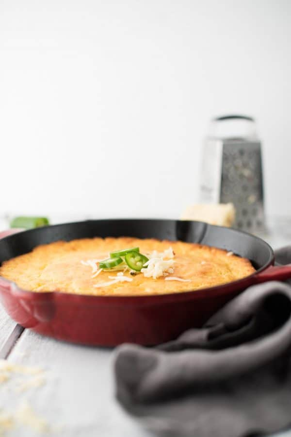 side view of cornbread in a red cast iron skillet