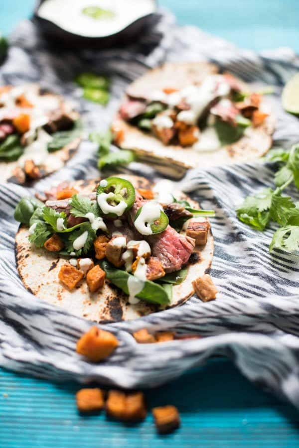 corn tortillas topped with flank steak, sweet potato and jalapeno crema