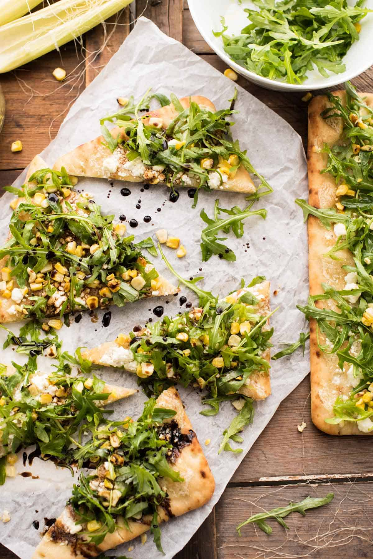 Simple Summer Flatbread with Grilled Corn, Arugula, Mascarpone + Goat Cheese. Just the right amount of crunch, creamy, sweet and savory - made in a flash!