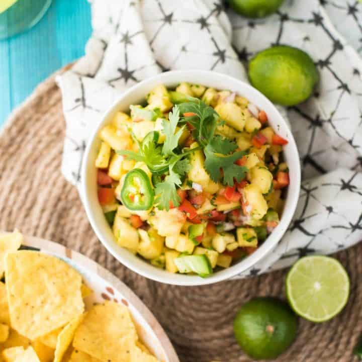 overhead view of pineapple salsa in a bowl surrounded by ingredients