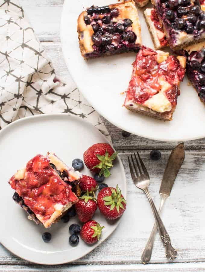 Red White and Blue Cheesecake Bars are a delicious Patriotic sweet treat with fresh summer fruit, creamy filling and crunchy gluten free crust.
