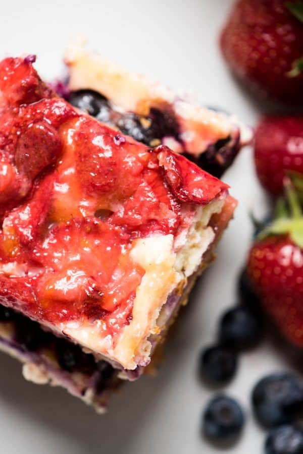 Red White and Blue Cheesecake Bars are a delicious Patriotic sweet treat with fresh summer fruit, creamy filling and crispy gluten free crust.