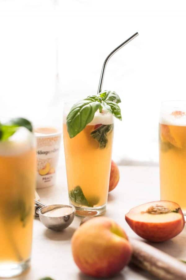 Summer Peach Basil Gin Floats are the perfect cocktail to beat the heat this summer. Frozen peach sorbet sweetens and chills herbaceous gin, fresh basil, and fizzy club soda. Not too sweet, incredibly refreshing. #cocktails #summer #gindrinks #poolparty #peach #basil #gin