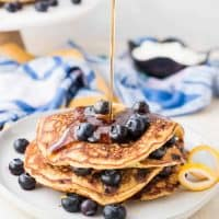 Maple syrup pouring onto blueberry pancakes