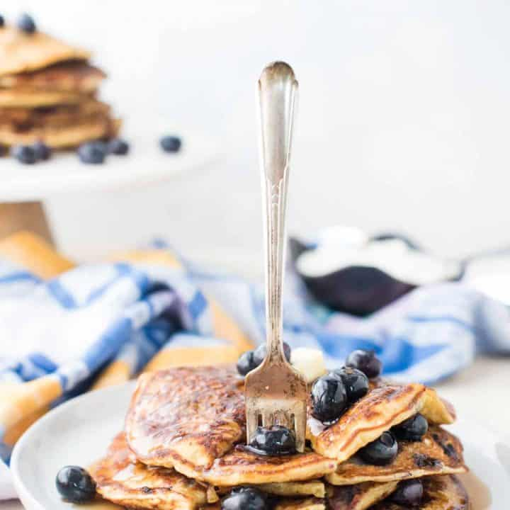 Stack of blueberry lemon pancakes with fork sticking out.