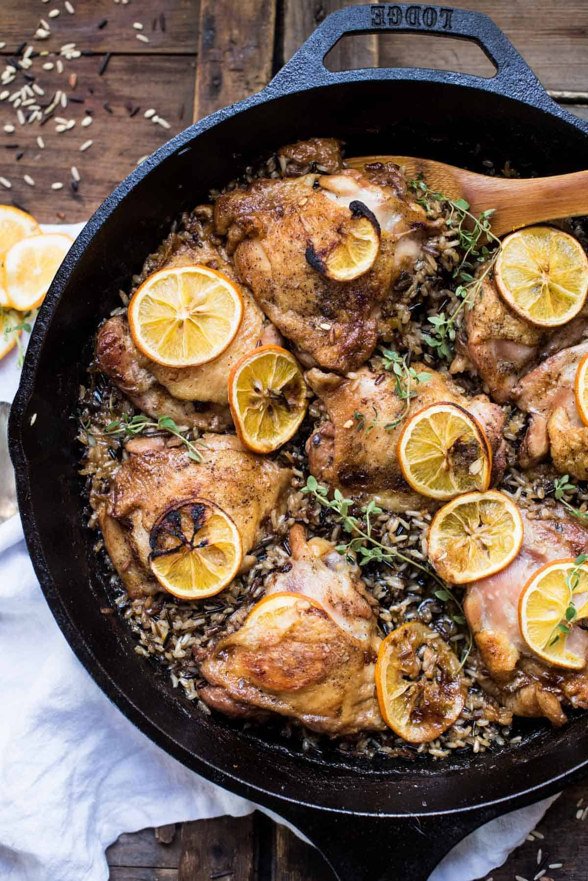 Crispy chicken thighs with lemon and wild rice in cast iron skillet