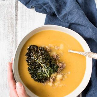 Overhead view of classic butternut squash soup with crispy kale