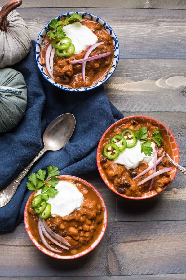 overhead shot of three bowls of pumpkin and beef chili