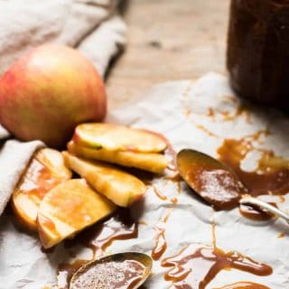 Spoons and apple slices covered in gooey salted caramel sauce