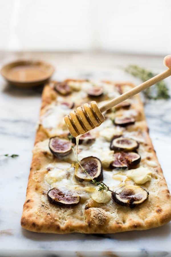 Honey drizzled over fig and goat cheese flatbread