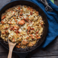 scooping lobster gratin out of a cast iron pan