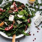 kale salad with pomegranate and blue cheese in a bowl