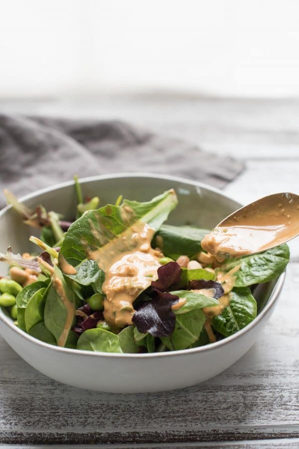 low calorie thai peanut dressing being spooned on top of a salad