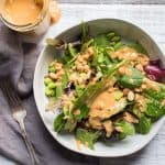 overhead photo of thai peanut dressing and a salad dressed