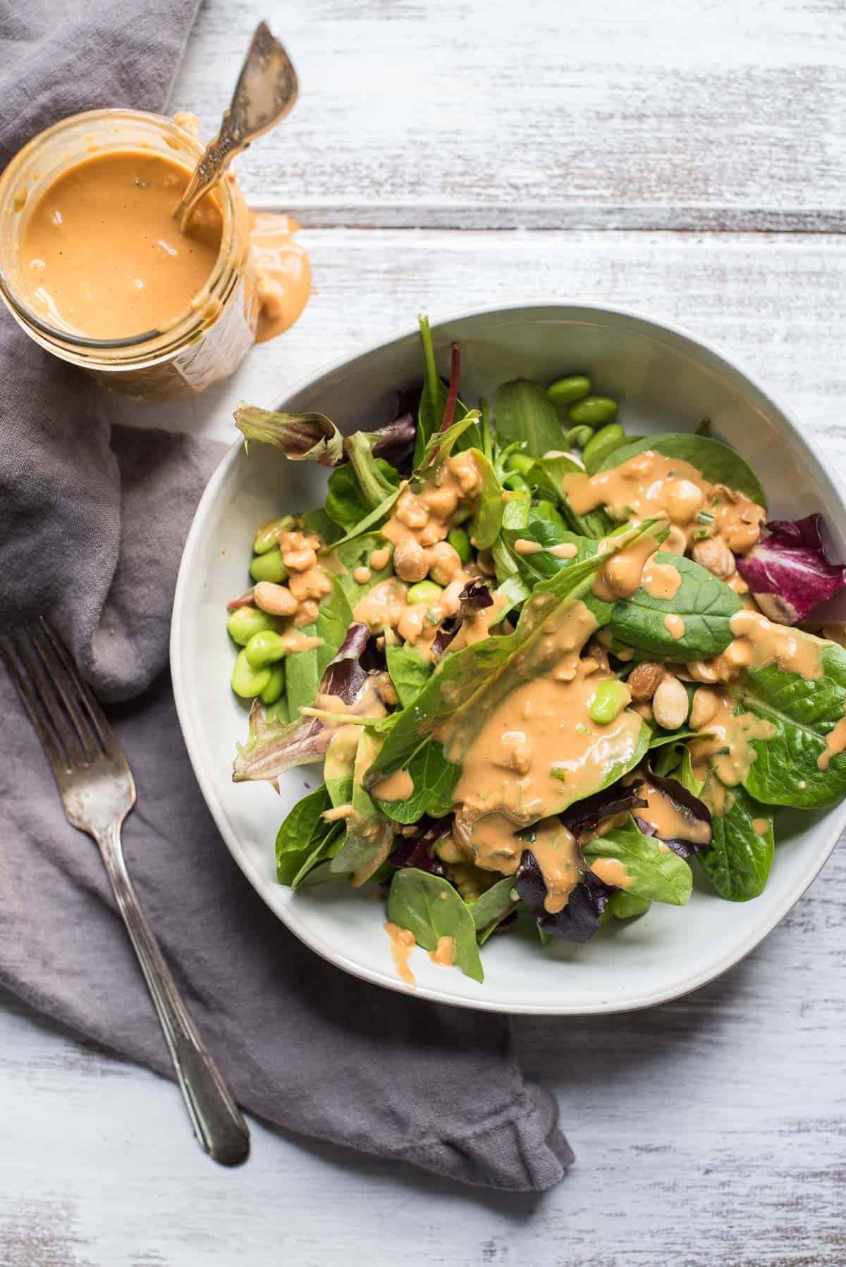 overhead photo of thai peanut dressing and a salad dressed