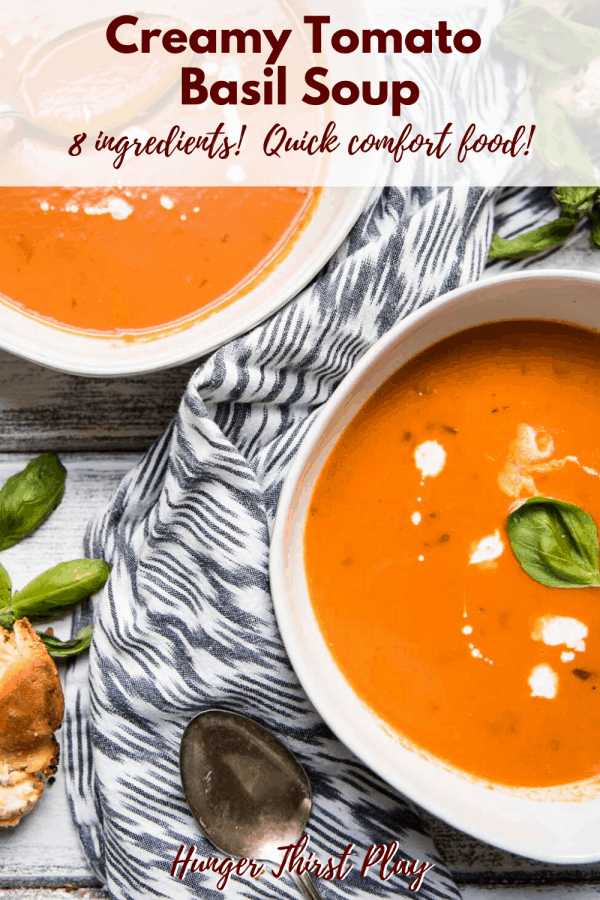 pverhead of bowls filled with tomato soup and drops of cream