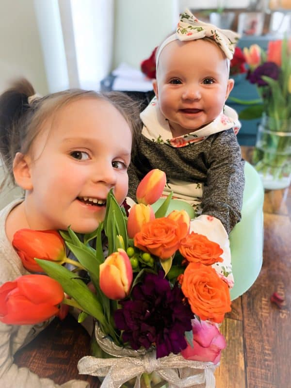 two small kids smiling with flowers