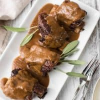 platter of guinness braised short ribs with smooth sauce reduction