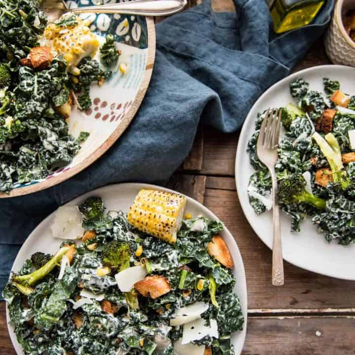 roasted broccoli and kale caesar salad in a bowl and plated on two plates