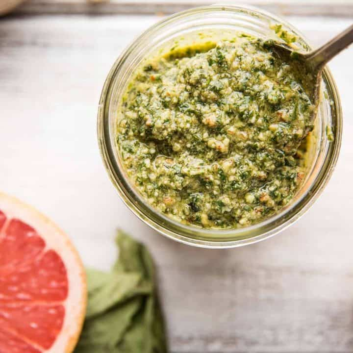Spoon scooping grapefruit basil pecan pesto out of a jar
