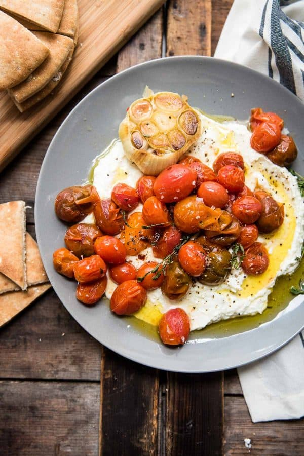 whipped feta topped with roasted garlic and blistered tomatoes on a grey serving plate