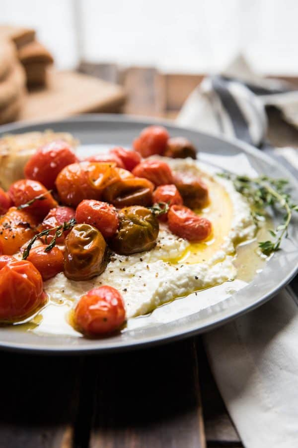 close up of blistered tomatoes and roasted garlic oil on top of creamy whipped feta