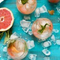 glasses of grapefruit sangria on a bright blue back drop