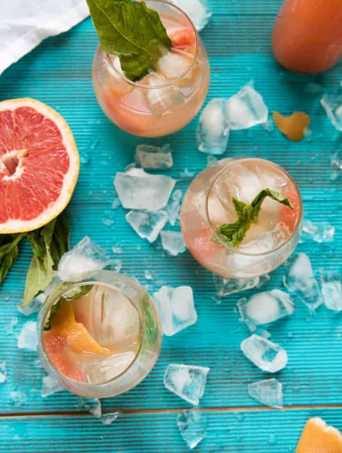 glasses of grapefruit sangria on a bright blue back drop
