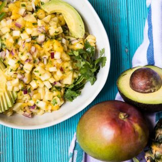 overhead view of pineapple mango salsa in a bowl with avocado
