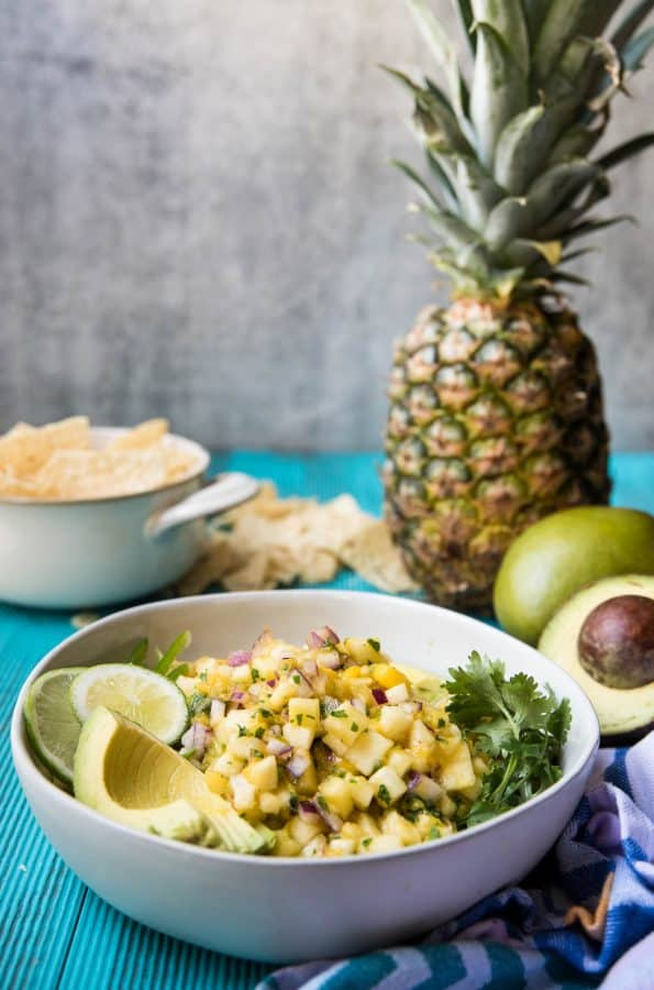 view of pineapple mango salsa in a bowl with chips