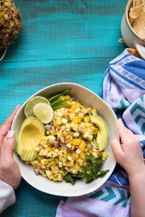 Mom and daughter hands grabbing bowl of pineapple mango salsa