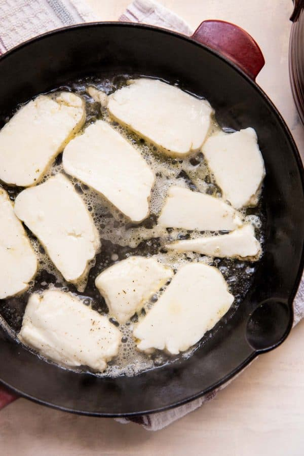 halloumi cheese frying in a cast iron skillet