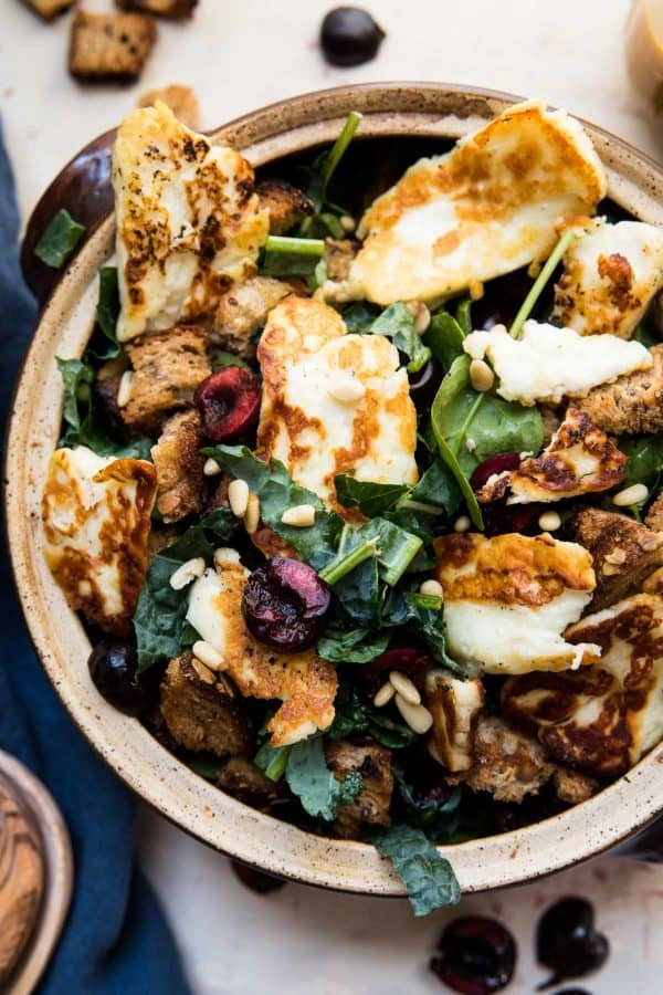 kale and spinach with cherries and fried halloumi in a bowl