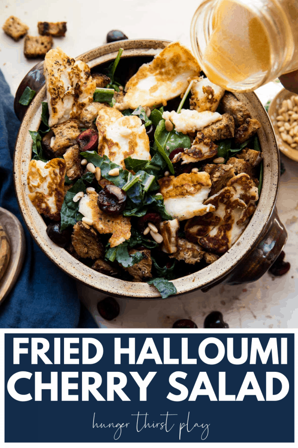 overhead photo of fried halloumi over spinach salad with fresh cherries