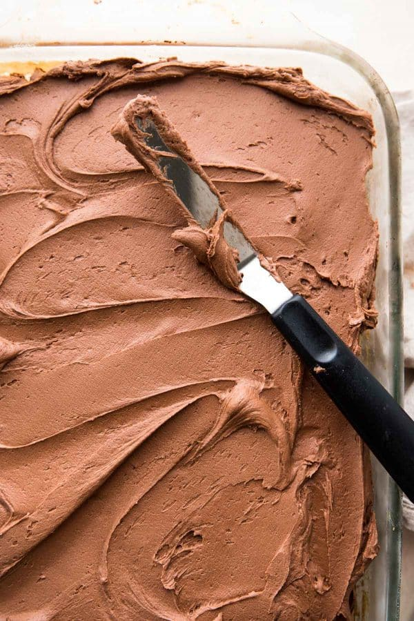 fluffy chocolate frosting spread onto sheet cake