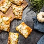 slices of squash flatbread on a dark background and pizza board