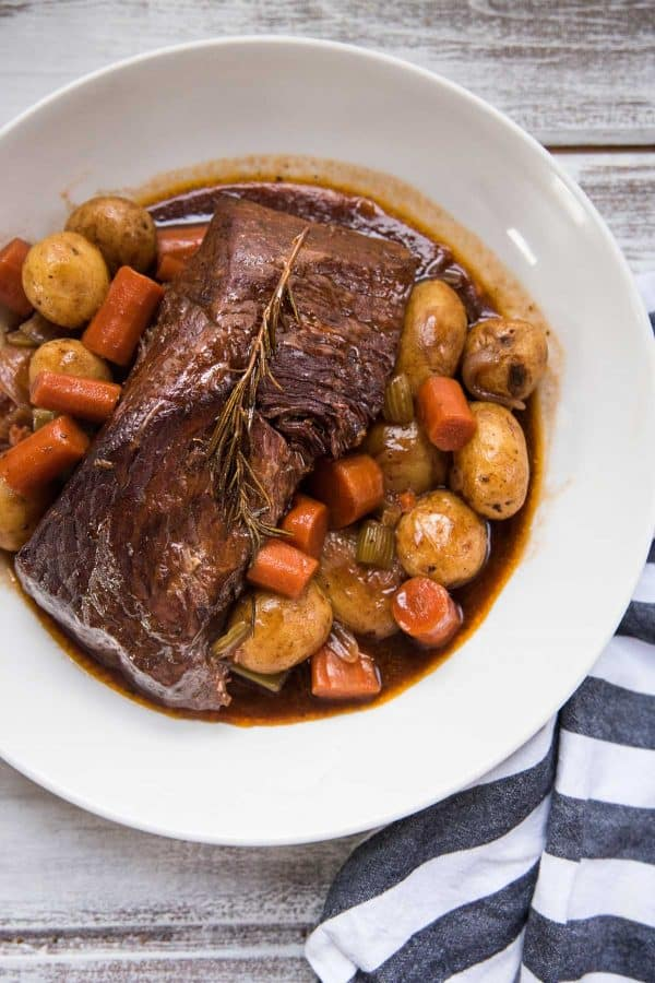 pot roast with vegetables and gravy in a serving platter
