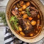 whole beef pot roast in dutch oven with vegetables and fresh herbs