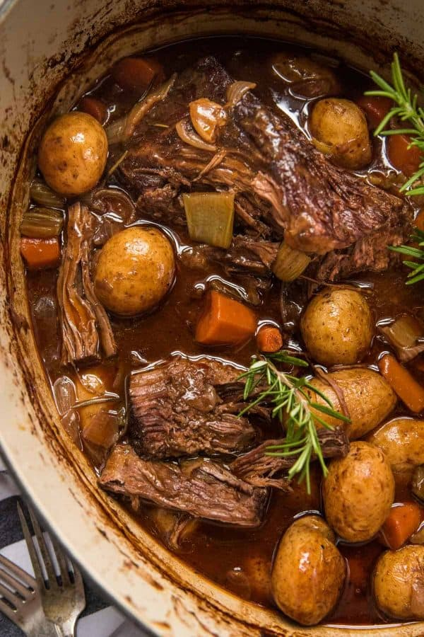 slightly shredded beef pot roast in dutch oven with vegetables and fresh herbs
